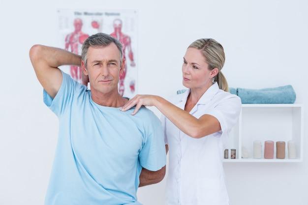 Medico che allunga il braccio di un uomo