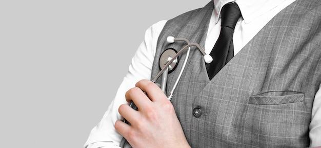 Medico in vestito che tiene uno stetoscopio grigio