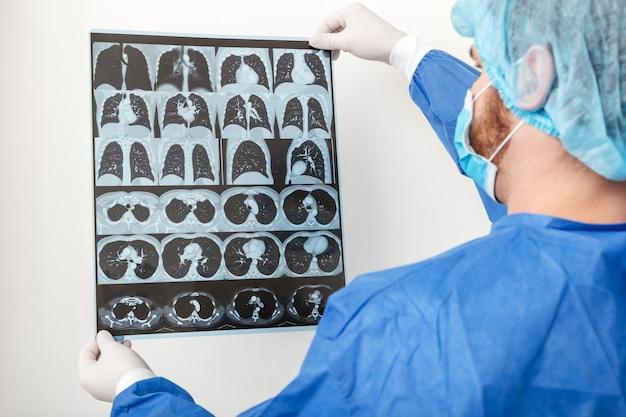 Medico chirurgo in uniforme protettiva controlla la radiografia del polmone alla risonanza magnetica. coronavirus covid 19, polmonite, tubercolosi, cancro ai polmoni, malattie respiratorie. concetto di medicina e assistenza sanitaria