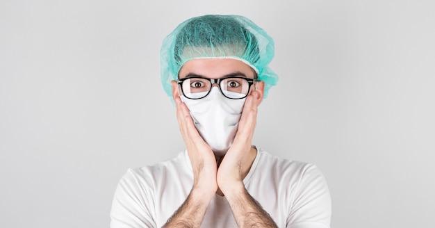 Medico chirurgo in maschera medica bianca e un berretto medico si leva in piedi su bianco con sorpresa, tenendo il viso con le mani.