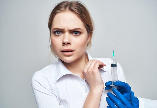 Siringa del medico in mano trattamento isolato sfondo