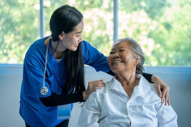 Medico che prende la torta di una donna anziana in ospedale, dottoressa asiatica si prende cura e discute con il paziente anziano in ospedale, concetto di assistenza sanitaria e di empatia.