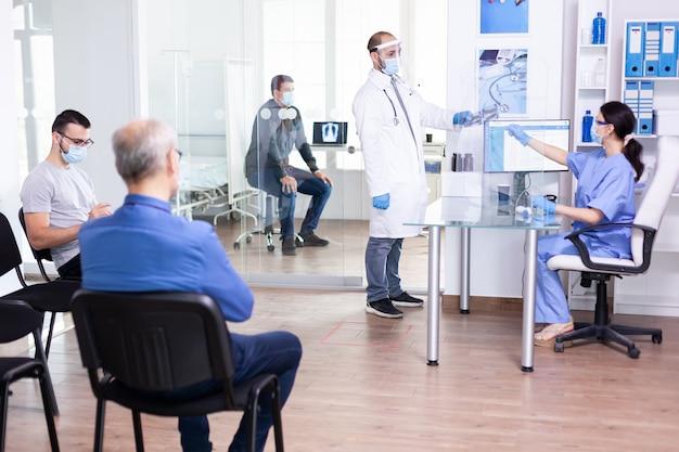 Medico che prende i raggi x del paziente dall'infermiera che indossa maschera facciale e visiera contro la pandemia globale di cornavirus e un gruppo di persone è in attesa di esame