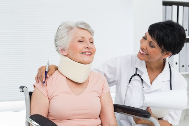 Medico parlando con un paziente anziano con collo cervicale