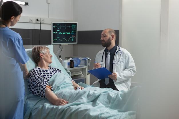 Dottore che parla con un paziente anziano seduto accanto al letto nella stanza d'ospedale, dando competenza per il trattamento