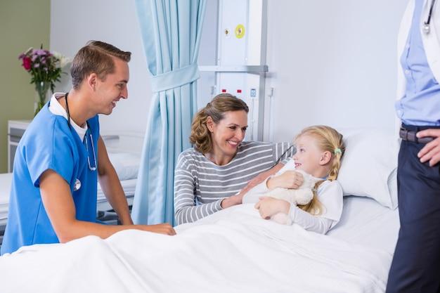 Aggiusti la conversazione con il paziente e la madre nella stanza di ospedale