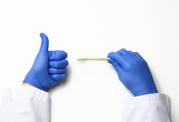 Il terapista medico è vestito con una veste bianca uniforme e guanti sterili blu in possesso di uno spazzolino da denti, concetto di spazzolatura quotidiana, sfondo bianco