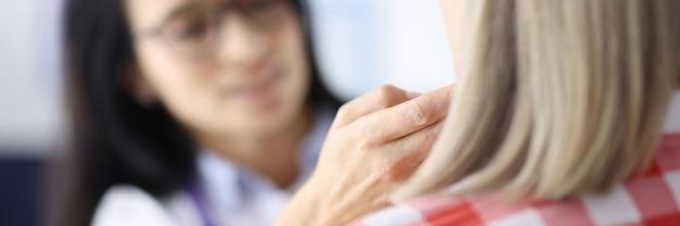Medico che tocca i linfonodi sottomandibolari dei pazienti con le mani in clinica oncologica