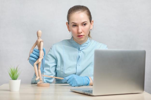 Il traumatologo medico conduce una lezione di videochiamata online attraverso un computer portatile.
