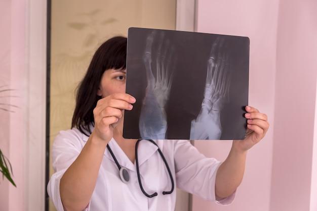 Medico traumatologo che esamina i raggi x del paziente in clinica