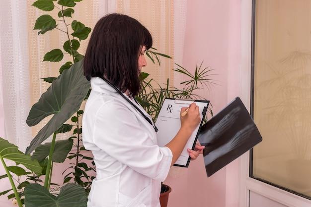 Il medico traumatologo con i raggi x del paziente sta riempiendo la prescrizione