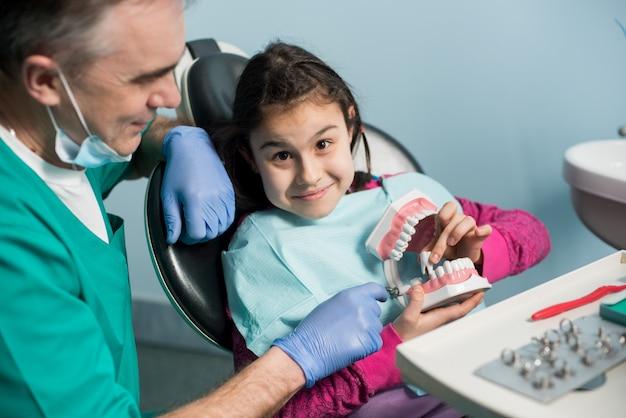 Medico che cura i denti della ragazza paziente presso studio dentistico