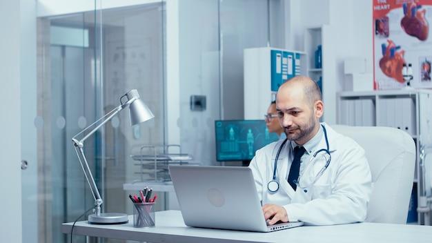 Dottore che digita un'e-mail dall'ufficio moderno della clinica privata con pareti di vetro, infermiera in background che controlla i raggi x, personale medico e pazienti che camminano in un corridoio affollato. consulto clinico del sistema sanitario
