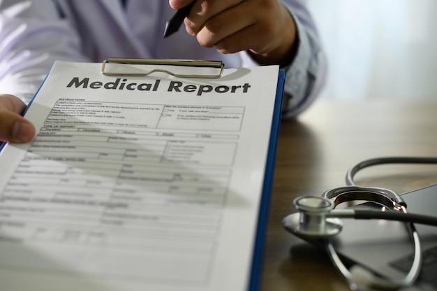 Medico che utilizza il referto medico della cartella clinica del computer o il database dei certificati medici dell'assistenza sanitaria del paziente