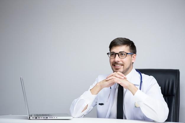 Medico che utilizza la tavoletta digitale trova informazioni sulla storia medica del paziente in ospedale. medico che utilizza uno stetoscopio per l'esame.