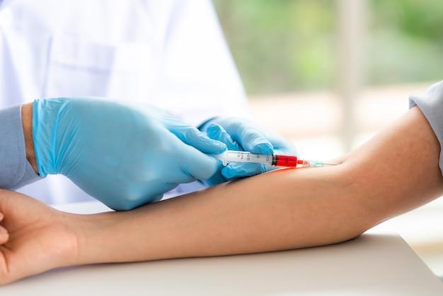 Il medico che usa la siringa prende il sangue dal braccio del paziente