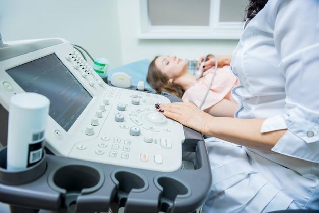 Medico che utilizza la macchina di scansione ad ultrasuoni per esaminare una tiroide di donna
