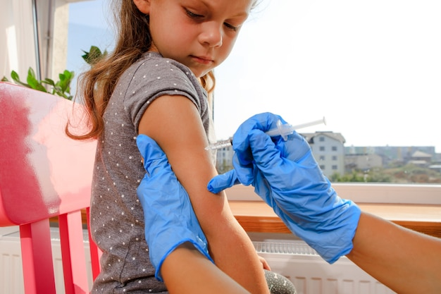 Medico che vaccina un bambino in una clinica moderna