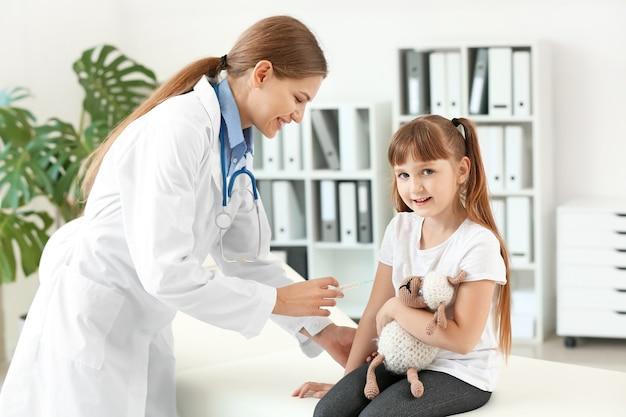 Medico che vaccina la bambina in clinica