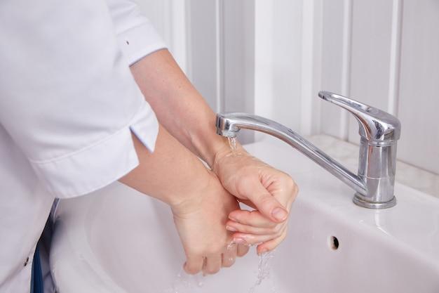 Il dottore si lava le mani sotto il rubinetto. primo piano delle mani delle donne.