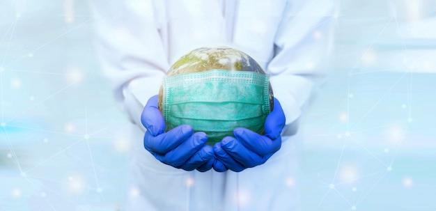 Il dottore indossa guanti tiene la maschera indossando la terra per salvare dal virus banner