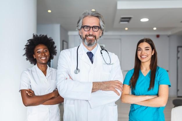 Il medico indossa l'uniforme medica bianca, lo stetoscopio e gli occhiali guarda la telecamera in posa in una clinica privata