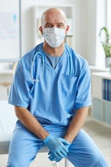 Medico che indossa l'uniforme blu, guanti in lattice e maschera sul viso seduto rilassato