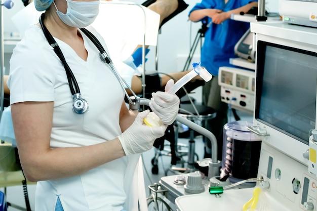 Un medico che indossa una maschera e guanti sta preparando attrezzature per la rianimazione per la ventilazione artificiale o...