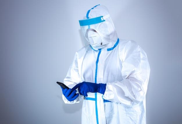 Il medico che indossa tuta protettiva medica, occhiali, maschera e guanti chiama al telefono. protezione dall'epidemia di virus. coronavirus (covid-19). concetto di assistenza sanitaria.