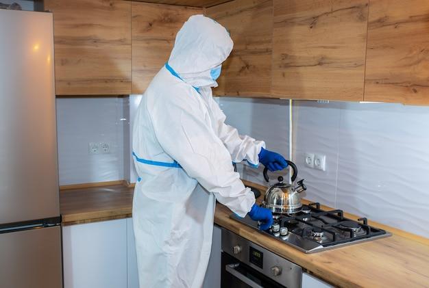 Medico che indossa tuta protettiva medica, occhiali, maschera e guanti che preparano il tè in cucina. teiera sul fornello a gas. protezione dall'epidemia di virus. coronavirus (covid-19). concetto di assistenza sanitaria.