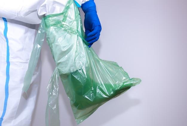 Medico che indossa tuta protettiva medica, occhiali, maschera e guanti. protezione dall'epidemia di virus. coronavirus (covid-19). concetto di assistenza sanitaria.