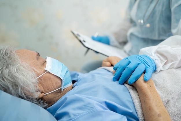 Medico che indossa una tuta ppe nuova normale per controllare la paziente asiatica anziana o anziana donna anziana che indossa una maschera facciale in ospedale per proteggere l'infezione covid-19 coronavirus.
