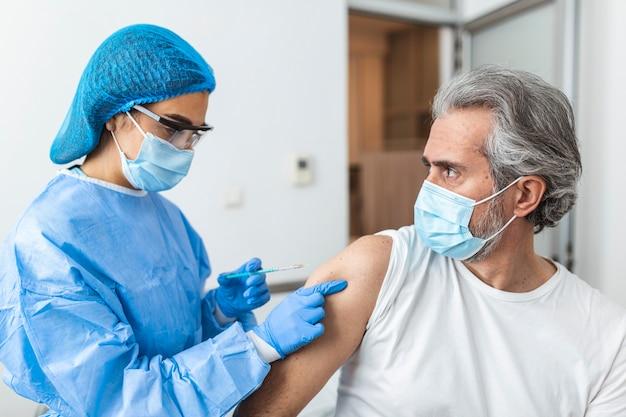 Medico che indossa tuta dpi e maschera chirurgica e usa il vaccino con il paziente infetto nella stanza di quarantena