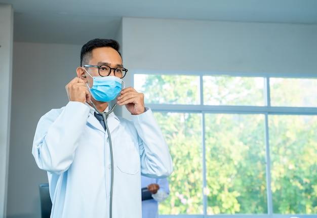 Medico che indossa una maschera protettiva per proteggere contro covid-19 in piedi con lo stetoscopio al concetto di ospedale, assistenza sanitaria e medicina.