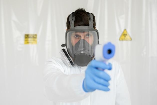 Medico che indossa una maschera protettiva pronto per l'uso del termometro a infrarossi sulla fronte per controllare la temperatura corporea per i sintomi del virus