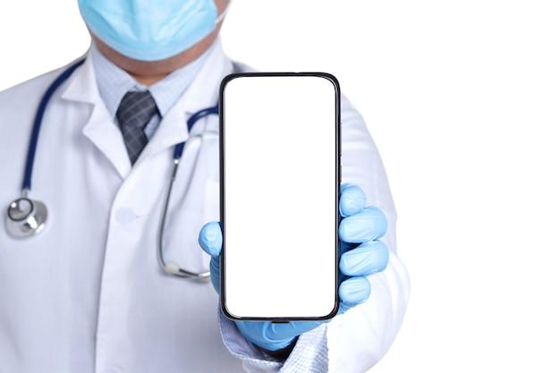 Medico che indossa una mascherina chirurgica che indossa guanti blu. tieni lo smartphone con uno schermo bianco.
