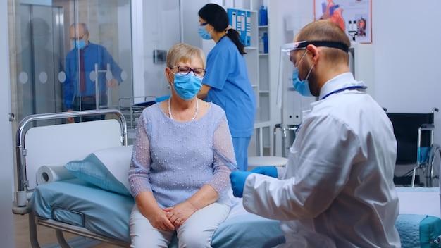 Medico che indossa una visiera che controlla la radiografia dei polmoni di una donna anziana in pensione nella moderna clinica ospedaliera privata. struttura sanitaria durante la pandemia globale covid-19, indossando dispositivi di protezione. medico