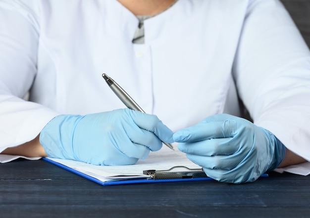 Un medico in camice bianco e guanti medici blu si siede al tavolo e scrive con una penna, da vicino