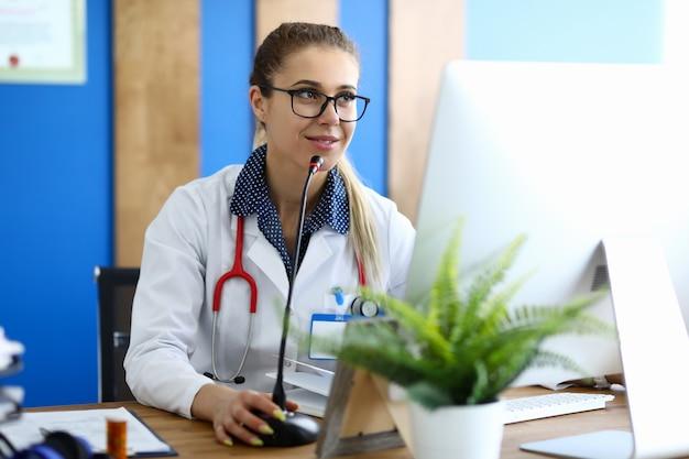 Il dottore in camice bianco offre una consulenza online tramite computer