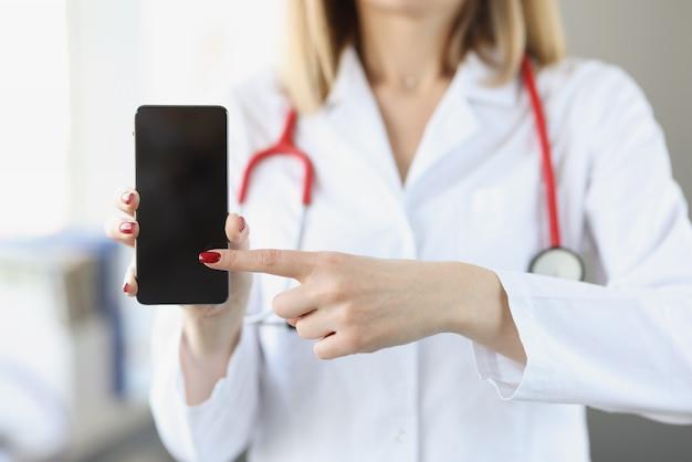 Il dottore in camice bianco tiene lo smartphone e lo punta con applicazioni mediche manuali per la cura