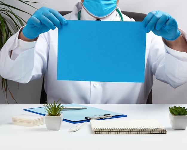 Il dottore in camice bianco è seduto a un tavolo su una sedia in pelle marrone e tiene in mano un foglio di carta blu vuoto, posto per un'iscrizione, studio medico