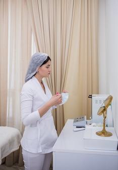 Un medico in uniforme bianca si alza e indossa una maschera protettiva usa e getta in ufficio