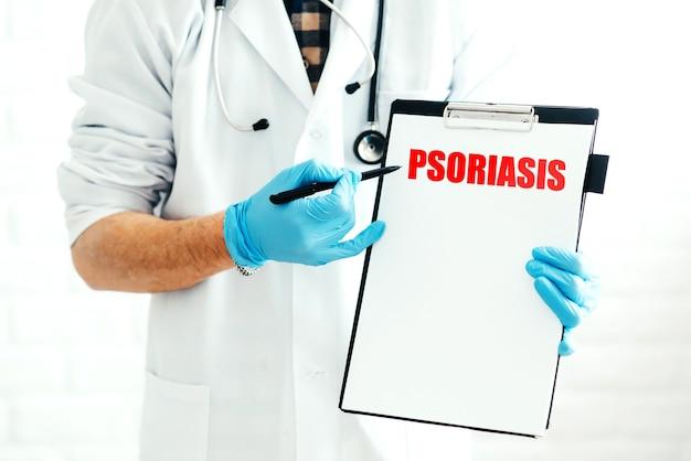 Medico con appunti su uno sfondo bianco con una penna mostra il nome della malattia psoriasi scritta in rosso