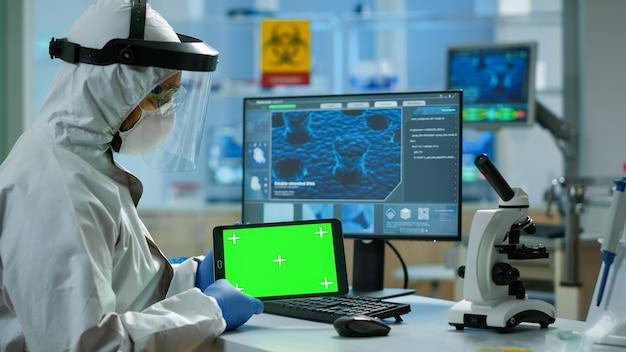 Medico con tuta che lavora al tablet con schermo verde in un moderno laboratorio attrezzato. team di microbiologi che effettuano ricerche sui vaccini scrivendo sul dispositivo con chroma key, isolato, display mockup.
