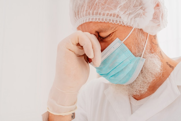 Il medico con maschera facciale e protezione per il viso è stanco della pandemia del virus covid