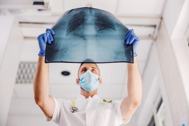 Medico con maschera facciale e guanti di gomma che esaminano i raggi x dei polmoni durante il virus corona.