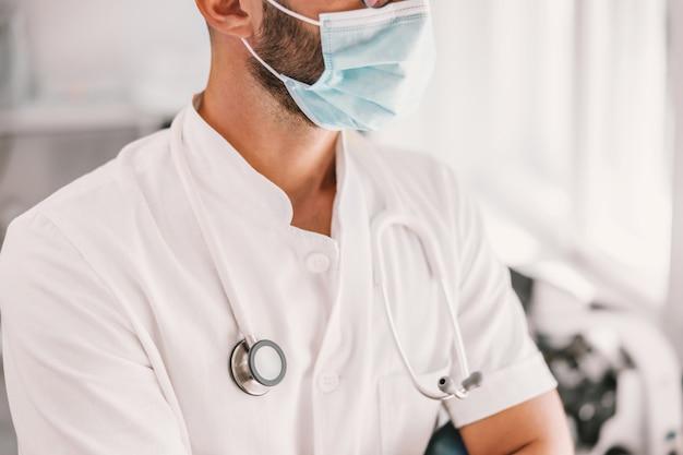 Medico con maschera facciale e stetoscopio al collo in piedi in ospedale durante il coronavirus