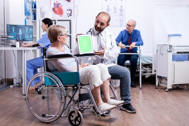 Medico con tablet con schermo verde nel centro di riabilitazione per pazienti disabili