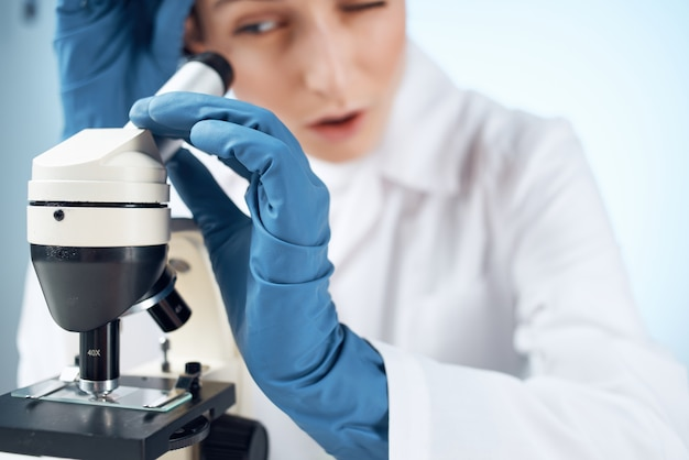 Medico con maschera medica che guarda attraverso un esperimento di laboratorio al microscopio. foto di alta qualità