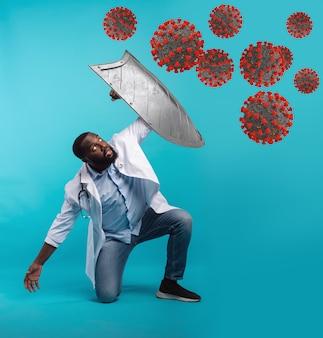 Medico con scudo di metallo che difende dalla malattia covida 19 sulla parete ciano